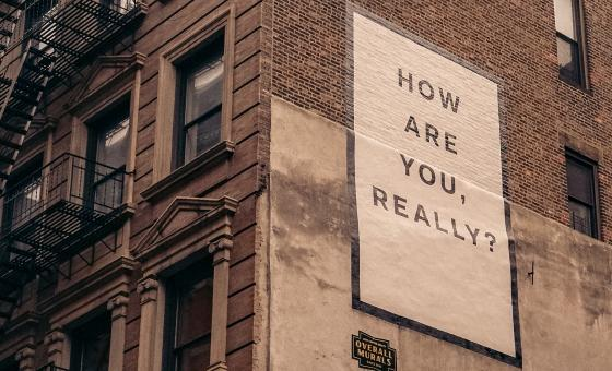 Sign on the side of a building that says How are you, really?