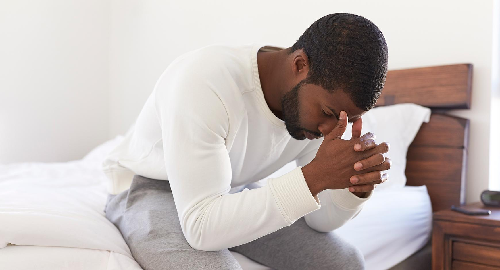 Depressed man looking unhappy sitting on side of the bed